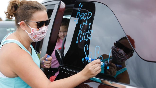 """Sarah Watson, a Jefferson High School math teacher, writes """"Keep Kids Safe!"""" on her vehicle's window on Monday in the parking lot of Rock Valley College before Watson about 100 others participated in a car caravan to protest of the reopening of schools this fall."""