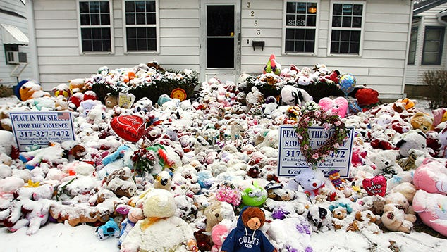 Hundreds of stuffed animals covered in snow sit in remembrance at 3283 Hovey Street