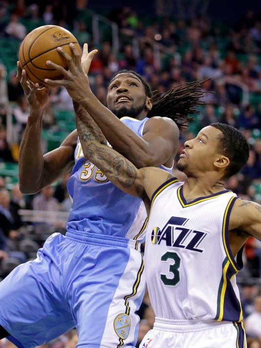 Utah Jazz's Trey Burke (3) defends against Denver Nuggets' Kenneth Faried (35) in the first half of an NBA basketball game Monday, Dec. 1, 2014, in Salt Lake City. (AP Photo/Rick Bowmer)