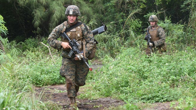 In this Nov. 7, 2016,  file photo, Marines break from the cover of the jungle during a demonstration at Andersen South in Yigo.  Guam needs more temporary workers than the federal government is allowing for the military buildup, according to Gov. Eddie Calvo.