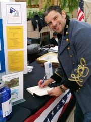 """Author Michael Gray signs a copy of his book, """"The Business of Captivity"""", about the Elmira Civil War prison camp, at an event Saturday at the Arnot Mall."""