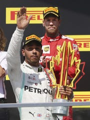 Mercedes driver Lewis Hamilton, foreground, of Britain, salutes the crowd after winning the Formula One Canadian Grand Prix auto race Sunday as second-place finisher Ferrari driver Sebastian Vettel, of Germany, looks on.