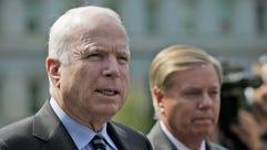 Sen. John McCain, R-Ariz., left, accompanied by Sen.