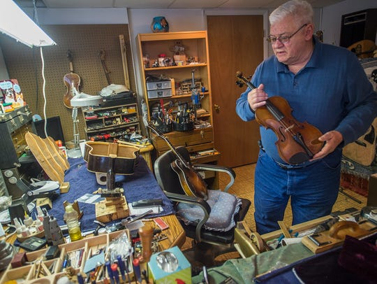Ken Pugh holds a violin in his hand inside of his shop