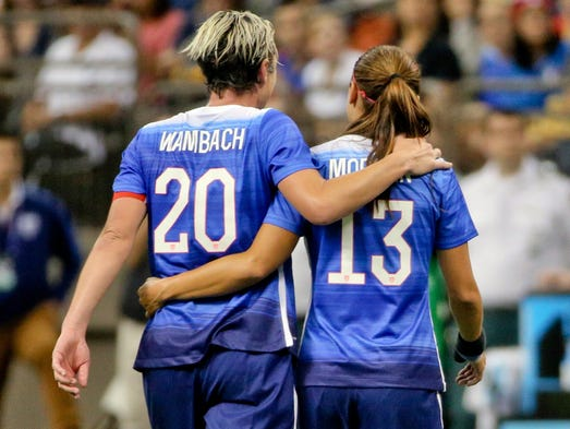 Abby Wambach (20) leaves the field with Alex Morgan