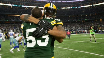 Green Bay Packers outside linebacker Julius Peppers (56) and outside linebacker Nick Perry (53) celebrate after beating the Dallas Cowboys in the NFC Divisional playoff game at AT&T Stadium.