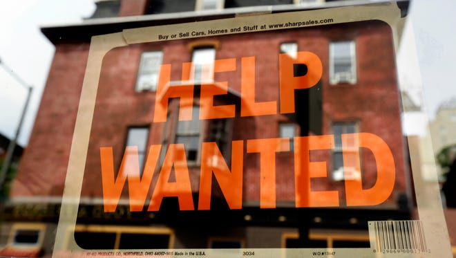In this August 2013 Associated Press file photo, a business displays a help wanted sign in its storefront.