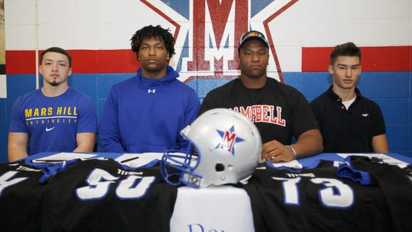 Four McDowell seniors signed to play college football on Friday - Tyler Banks, Tre Spearman, Isaiah Burch and Chase Justice, from left to right.