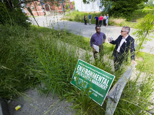 Michael Osborne, right, president of the Near North Development Corp., and James A. Whitfield, of the Highland Vicinity Neighborhood Association, discussed an overgrown property on Indianapolis' Near Northside in 2013.