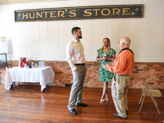 Les McCall, left, chats with Nikki Saylors, middle, Bart Garrison Agriculture Museum educator, and Nick Fletcher, right, after a press conference at Hunter's Store in downtown Pendleton on Friday.