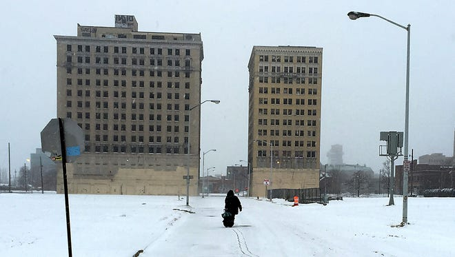 Luvenia Ryans pulls her bag in the snow up Sproat Street towards the vacant Park Avenue Hotel and the Eddystone Hotel in Detroit as she walks to church from her Brush Park home on Sunday, Feb. 1, 2015.