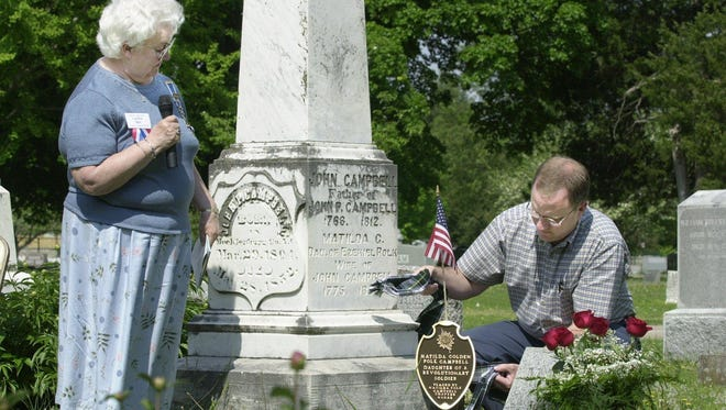Ron Hutcheson, a member of Sons of American Revolution, unveils a grave marker for Matilda Polk Campbell while Carolyn Mott, regent of Matilda Polk Campbell Chapter DAR, looks on during the dedication ceremony at Hazelwood Cemetery in 2001.