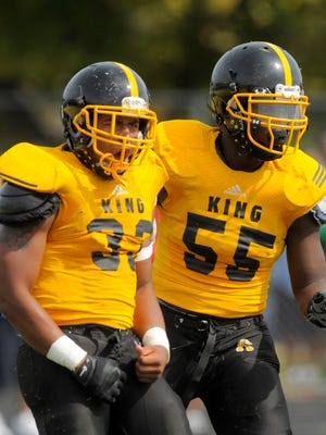 Lawrence Bryant (33) and Justin Turner (55) celebrate a tackle for loss during King's win over Cass on Sept. 26.