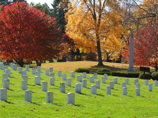 Fall colors make a splash and dramatic backdrop to veteran's graves at Crown Hill Cemetery Wednesday, October 22, 2014.
