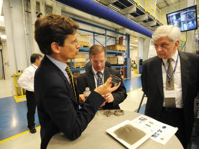 Miba Friction Group CEO F. Peter Mitterbauer talks with Austrian Ambassador Hans Peter Manz on Thursday in the company's McConnelsville plant. The company produces automobile parts by compressing the metal powder in the bowl on the table.