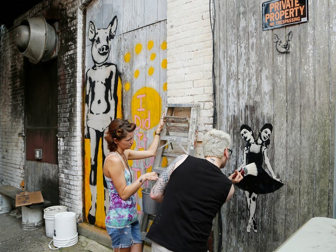 "AnnaLynn McKane assists Craig Tribble on Friday as he uses wheat paste to secure a print called ""The Strange Girls"" on the back of Lafayette Brewing Co. The work is adjacent to ""I Did it for the Lulz,"" also by Tribble."