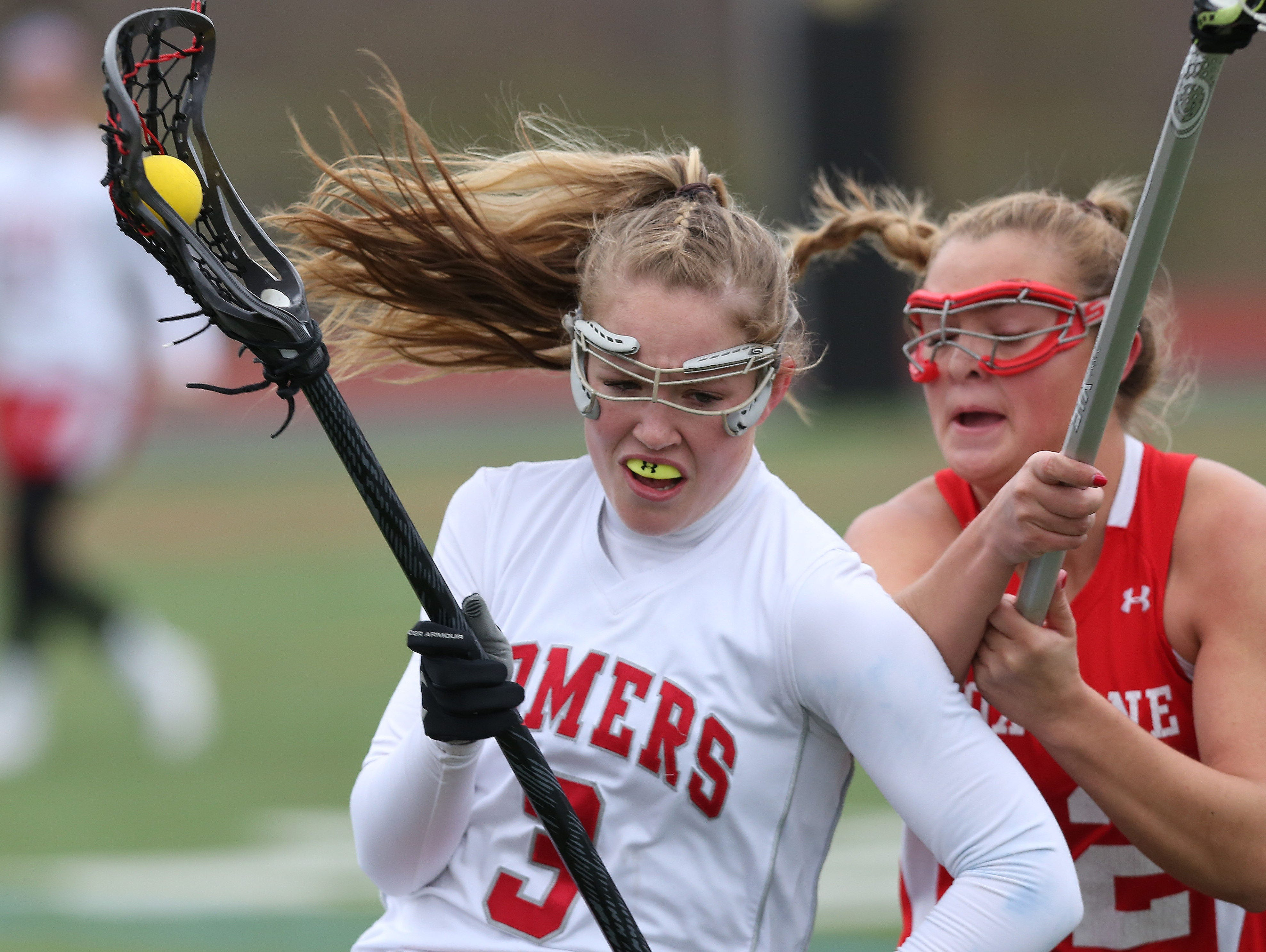 Somers' Gabby Rosenzweig (3) tries to get around Fox Lane's Lindsey West (12) during a girls lacrosse game at Somers High School April 8, 2016. Somers won the game 15-12.
