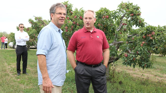 Dan Bergman, left, owner of Bergman Orchards, discusses his growing techniques and business with Ohio Senate Pres. Keith Faber, right.