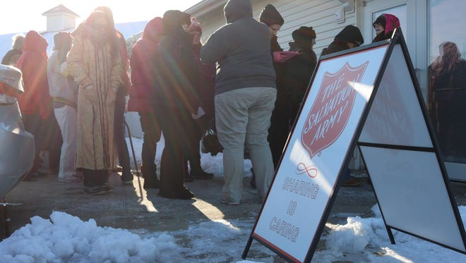 Local families from throughout Ottawa County brave frigid temperatures while waiting in line to select Christmas gifts for their children with the Salvation Army's Toys for Tots program.