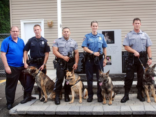 From left, Union County Sheriff Joseph Cryan congratulates Mansfield Township Police Officer Gregory Zytko and K9 Jax, New Jersey Park Police Officer Rolando Rodriguez and K9 Cabo, Union County Sheriff's Officer Ashley Current and K9 Sam, New Jersey Park Police Officer Karl Mott and K9 Kelly, and New Jersey Park Police Officer Kenneth Kriete and K9 Zico on graduating the Union County's Sheriff's Office K9 Training Academy during the graduation ceremony for Class 16-01 in Summit.