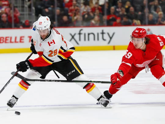 Calgary Flames center Dillon Dube (29) protects the puck from Detroit Red Wings left wing Tyler Bertuzzi (59) in the second period of an NHL hockey game Sunday, Feb. 23, 2020, in Detroit. (AP Photo/Paul Sancya)