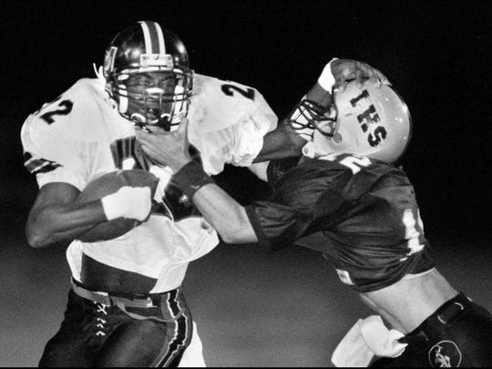 Umatilla's Johnny Williams uses a stiff-arm to try to fend off LaBelle's Brandon Rimes, who was determined to bring down the powerful runner during their 1995 matchup.