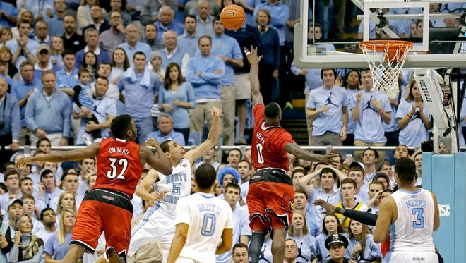North Carolina's Marcus Paige (5) shoots the game winning basket as Louisville's Chinanu Onuaku (32) and Terry Rozier (0) defend during the second half of an NCAA college basketball game in Chapel Hill, N.C., Saturday, Jan. 10, 2015. North Carolina won 72-71. North Carolina's Nate Britt (0) and Kennedy Meeks (3) watch. (AP Photo/Gerry Broome)