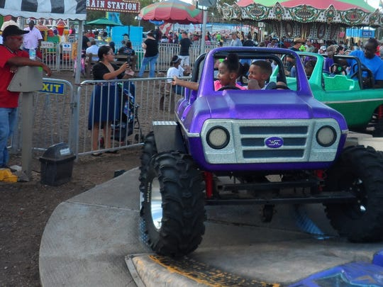 Dylan Green (right), 7, and his sister, Karlei Hall, 3, ride the Monster Trucks ride Sunday at the Rapides Parish Fair.