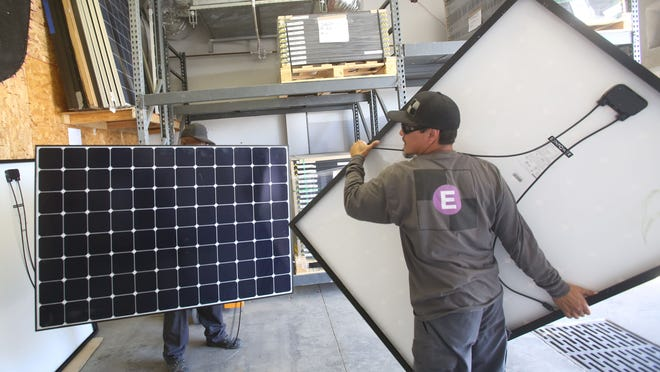 From left, Charly Evans, warehouse manager for Hot Purple Energy, and crew installer Nick Hernandez arrange panels at the Palm Springs firm.