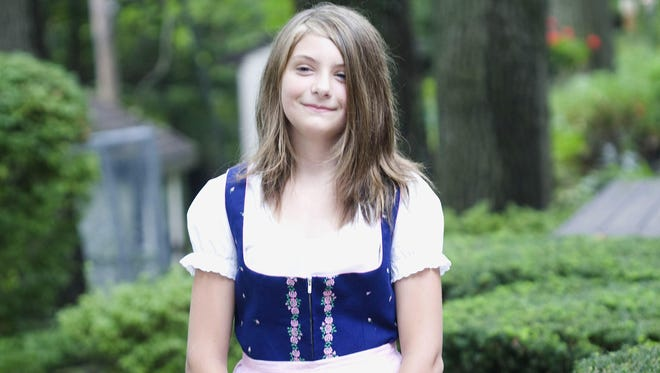 Kennis Cady, in a photo taken when she was 11 years old, wears a dress that has been passed down for generations in her family. Kennis died July 29, 2015, after being in a coma for seven days.