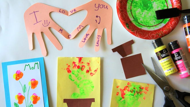 With some construction paper, glue and paint or markers, you can help your child make a Mother's Day card.