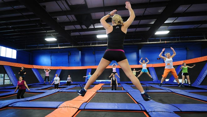 "Instructor Lora Smith, center foreground, warms up her class on trampolines at the start of their ""skyrobics"" class at Fishers Sky Zone in Fishers, Ind., on March 13, 2012."