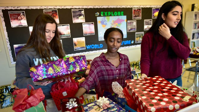 CASHS students are stuffing stockings for the holidays that will be given to people at the Children's Aid Society and other places that fill the need. Katelyn Hottle, left, Hermela Amdeta and Zainab Jawad sort gifts in a CASHS classroom.