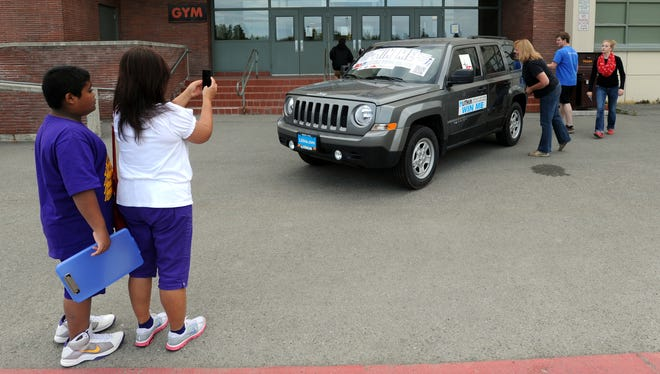 Arceli Carreon pauses for a photo Aug.  6, 2013, as students and parents arriving for registration at West High School take a look at a Jeep Patriot an Anchorage, Alaska,  School District student will win following a year of perfect attendance.