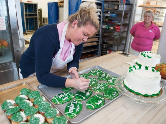 McMillan's Bakery employee Amanda Clark decorates Eagles themed cookies as manager Kristine Emmons looks on at McMillan's Bakery in Haddon Township.