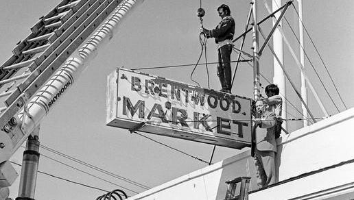 Brentwood City Manager Cecil Wray, in suit, gives a little high-level assistance to Danny Mayes, left, and Earnest Dean as they lower the Brentwood Market sign, one of seven large signs removed from the business district along U.S. 31 May 4, 1973 in compliance with a new city zoning ordinance.