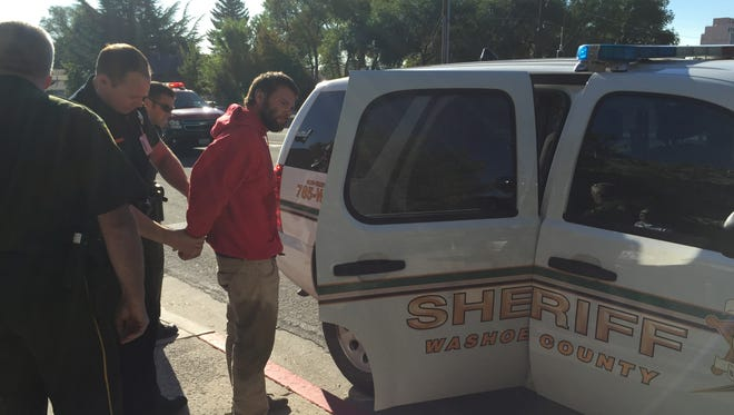 Washoe County deputies arrest a man after he threatened to drink from a Round Up bottle during a public meeting on Monday.