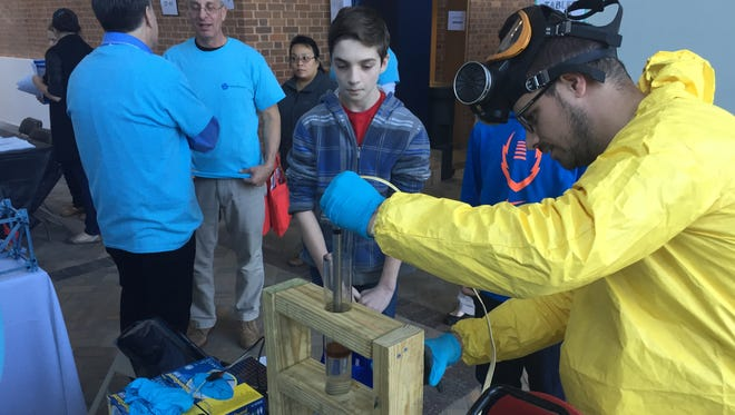 Students watch a science demonstration at the booth for the Delaware STEM Academy at the Public School Choice Expo on Saturday.