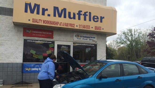 Mr. Muffler manager Bob Makins helps a customer with a repair Saturday.