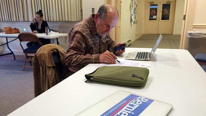 In this May 9, 2016, photo, Leslie Lakind, foreground, and Navona Gallegos, background, speed-dial potential voters on behalf of the Bernie Sanders campaign at a public library in downtown Santa Fe, N.M. The divide between Democrats in the presidential primary race is on stark display in New Mexico, where voters go to the polls on June 7. Sanders supporters have been speed-dialing the nation from cafes, libraries and union halls and are not about to give up before the final round of state primaries. Hillary Clinton holds the advantage nationally and has locked in support from New Mexico superdelegates and other local powerbrokers.