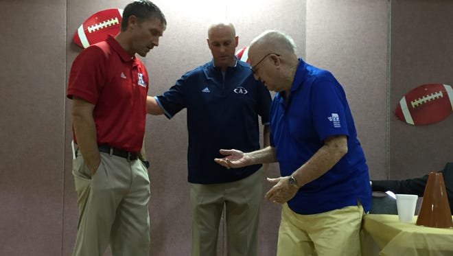 Haughton coach Jason Brotherton and Airline coach Bo Meeks check out the coin toss of Bossier Lion's Club member M.D. Ray Monday at Airline Baptist Church. The Vikings won the toss.