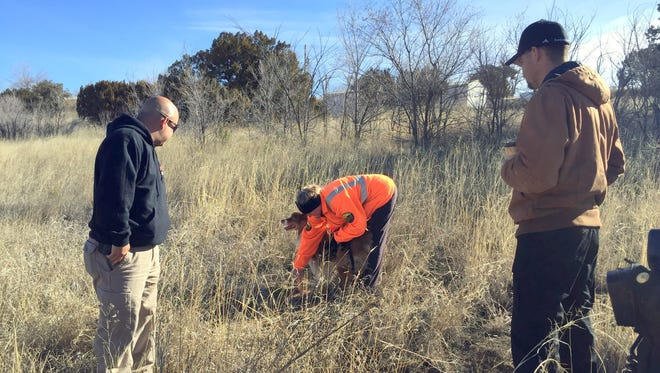 A member of the Grant County Search and Rescue Team, Shari Chandler, marks the spot where her cadaver dog indicated there was a possible human remains Tuesday morning in the Village ofSanta Clara while Hector Carrillo, left, of the Grant County Sheriff's Department looks on as well as Ben Villegas of the Silver City Police Department.
