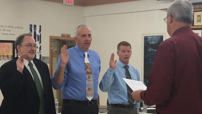 Jan Cahill (left), Don Ryan and Jason Brantley are sworn in as trustees of the school board.