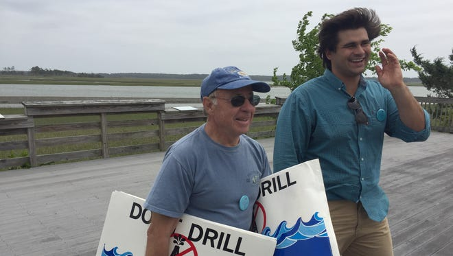 Bill Mastyl, left, with Virginia Eastern Shorekeeper Jay Ford, right, carries signs protesting offshore oil and gas drilling after an event held Saturday, May 20, 2017 at Willis Wharf, Virginia.