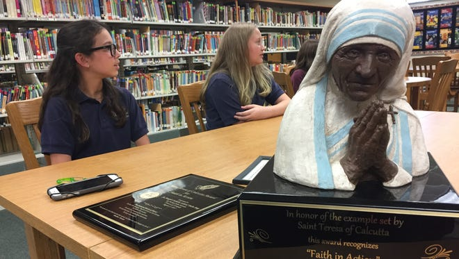"""Sixth-grade students Madeline Pesi (left) and Zoey Cook discuss their school's endeavor to help the homeless. The diocese awarded St. Joseph's Catholic School the Mother Teresa """"Faith in Action"""" award."""
