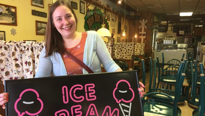 Yum Yum Tree owner Allison Austin holds up the ice cream sign that once hung in the now-closed Brighton restaurant and ice cream parlor, Monday, May 7, 2018.