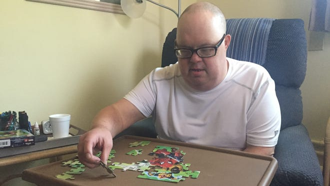 George 'Georgie' Gillette works a Spiderman puzzle May 7, 2018, at his sister's home in Sebastian. Gillette, 49, has Down syndrome and is at the center of a visitation dispute involving his two sisters and an Indian River County public guardian.