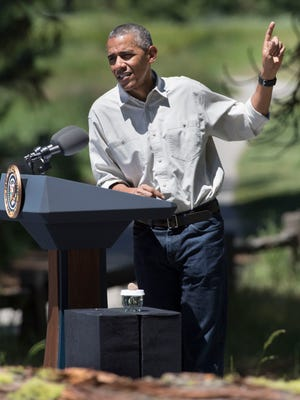 President Barack Obama gestures to Yosemite Falls while speaking to a small group of invited guests and the media during his visit to Yosemite National Park on Saturday, June 18, 2016.