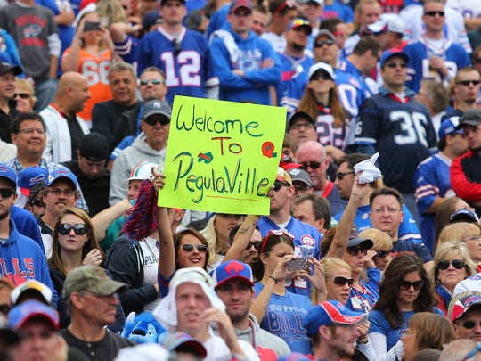 A fan holds a sign celebrating Terry and Kim Pegula during an NFL game on Sept. 14, 2014.