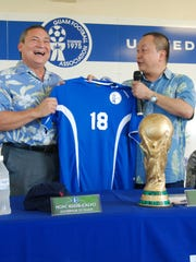 In this file photo, Gov, Eddie Calvo, left, and Guam Football Association President Richard Lai with a Matao team jersey and a replica FIFA World Cup trophy after signing a land lease agreement to build a second soccer complex in the southern half of the island.